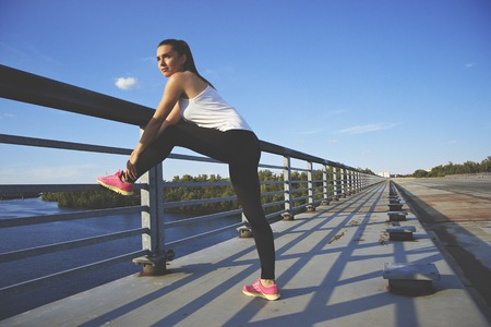 Good day for training. Horizontal shot of confident, beautiful and young woman in sports clothing holding leg and looking away while doing stretching on bridge with blue sky on background. Zdjęcie Seryjne