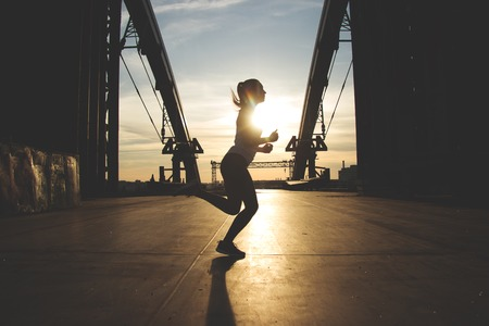 She loves evening jogging. Side view shot of young beautiful woman in sports wear running on the bridge during sunset with industrial view on background. Zdjęcie Seryjne