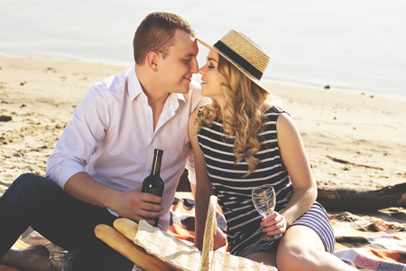Beautiful love story. Horizontal shot of beautiful young woman sitting close face to face with her boyfriend and smiling while having picnic on the beach. Zdjęcie Seryjne