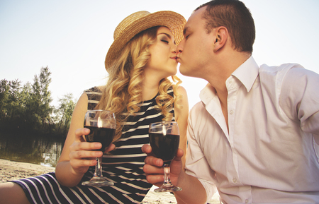 Love to kiss her lips. Portrait of man in casual wear kissing his young beautiful woman in dress and keeping glasses with wine in their hands while having picnic on beach.