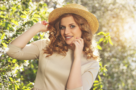 Beautiful and natural. Portrait of attractive young woman in dress adjusting her hat and smiling while posing with blossoms tree.