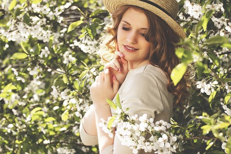 Tenderness and charm. Side view portrait of beautiful and young woman in dress and hat keeping eyes closed and smiling while standing among blossoms tree.
