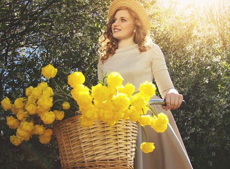 Fascinating girl. Portrait of beautiful and young woman in dress and hat looking away and smiling while keeping bike with flower basket on it. Zdjęcie Seryjne