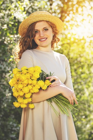 Girl love flowers. Portrait of attractive and young woman in dress and hat keeping flowers in hands and smiling while standing against blossoms tree.
