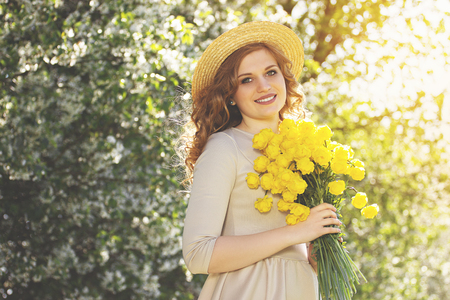 Flowers make girl happy. Portrait of beautiful young woman in dress and hat keeping flowers in hands and smiling while standing against blossoms tree. Zdjęcie Seryjne