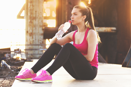 Staying hydrated. Beautiful young woman in sports clothing drinking water while having rest after workout. Evening sunlight and industrial view on background.