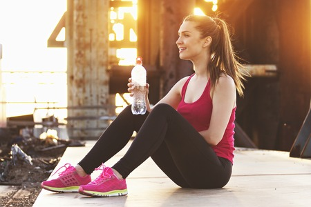 Keeping good water balance. Young beautiful woman in sports wear keeping bottle with water in hand and smiling while sitting on bridge with industrial view on background.