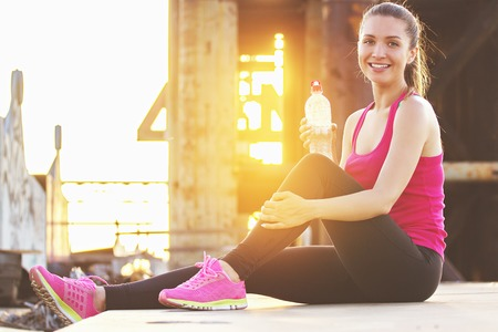 Having rest. Cheerful, beautiful and young woman in sports clothing looking to camera and smiling while stretching after workout on bridge with evening sunlight on background. Zdjęcie Seryjne