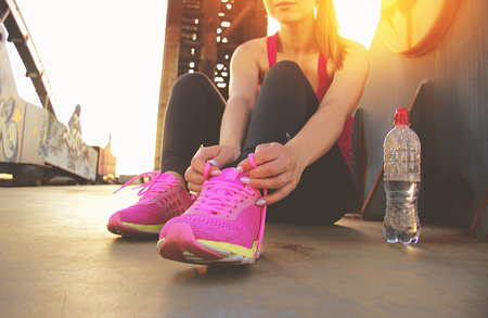 Time for brake. Cropped image of young beautiful woman in sports wear tying shoelaces while sitting on bridge with evening sunlight on background. Bottle with water is nearby.
