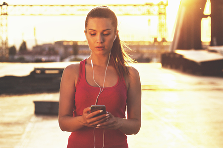 Gadgets for sports. Portrait of confident beautiful woman in sports clothing using smart phone while standing on bridge with evening sunlight on background. Zdjęcie Seryjne