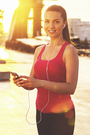 Motivational music. Attractive young sports woman looking to camera and smiling while using phone during workout on bridge with sunlight and urban view on background.