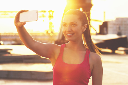 Sports selfie. Young and beautiful woman in sports wear looking at phone and smiling while taking selfie on the phone with evening sunlight on background.