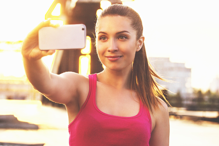 She loves selfie. Portrait of young and attractive woman in sports clothing looking at phone and smiling while taking selfie on her phone during outdoors workout.
