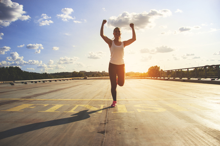 Winner as style of life. Horizontal shot of young beautiful woman in sports clothing keeping arms raised and smiling while passing finish line during jogging. Evening sunlight on background. Фото со стока - 83547835