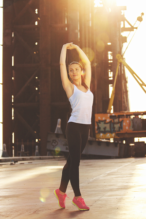 Outdoor exercising. Full-length shot of attractive young woman in sports clothing keeping arms raised and looking away while doing stretching on bridge with evening sunlight on background.