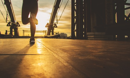 Workout in the city. Cropped silhouette image of beautiful young woman jogging on the bridge with industrial view and evening sunlight on background. Zdjęcie Seryjne