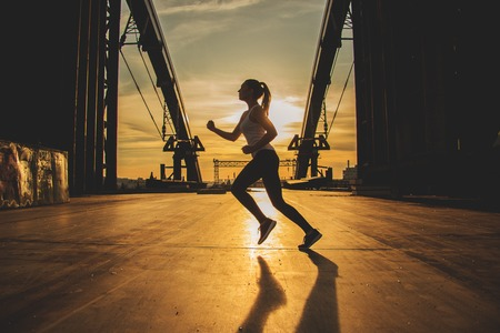 Evening jog. Side view of young attractive woman in sports clothing jogging on the bridge with industrial view and sunlight on background. Zdjęcie Seryjne