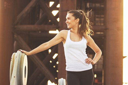 Have a brake after good workout. Portrait of attractive young woman in sports wear looking away and smiling while standing on the bridge.