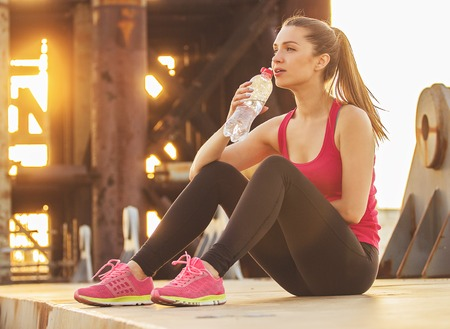 Keeping water balance. Horizontal shot of beautiful young woman in sports wear looking away and drinking water after jogging while sitting on the bridge.