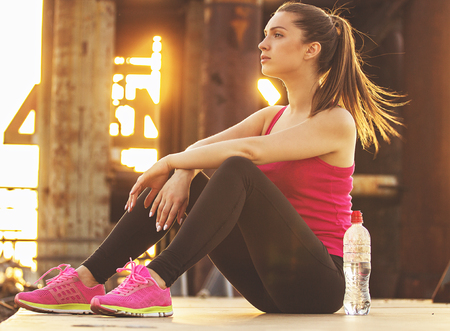 Relaxing after good workout. Side view of attractive young woman in sports clothing looking away while sitting on bridge after long jog.