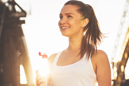 Cheerful fitness girl. Low angle view of young attractive sports woman looking away and smiling while drinking water on the bridge with sunlight on background. Zdjęcie Seryjne