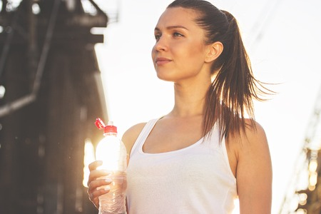 That was great workout. Low angle view of beautiful young sports woman looking away while drinking water after evening jog on the bridge with sunlight on background.