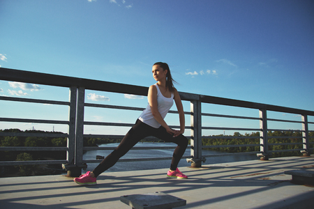 Warming up before workout. Horizontal shot of beautiful young woman in sports wear looking away while doing stretching on the bridge with blue sky on background.