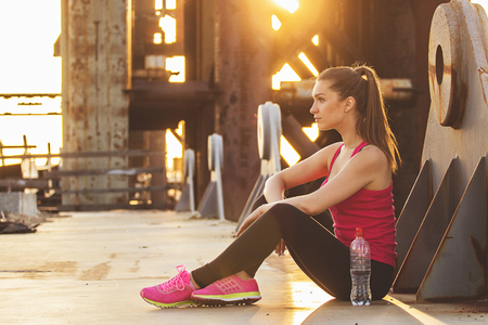 Resting after evening jog. Side view of attractive young woman in sports wear looking away while sitting on the bridge with evening sunlight and industrial view on background. Zdjęcie Seryjne