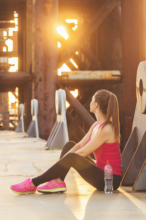 Take a brake. Side view of beautiful young woman in sports wear looking away while sitting on the bridge with evening sunlight and industrial view on background. Zdjęcie Seryjne