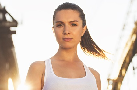 Confident sports woman. Portrait of young and attractive woman in sports clothing looking to camera while standing on bridge with sunlight on background. Zdjęcie Seryjne