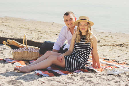 Happy together. Horizontal shot of beautiful and young couple looking to camera and smiling while sitting on the beach during picnic.