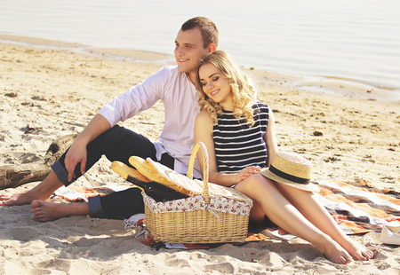 They are in strong love. Horizontal shot of young and beautiful couple looking away and smiling while sitting on the beach and having picnic. Zdjęcie Seryjne