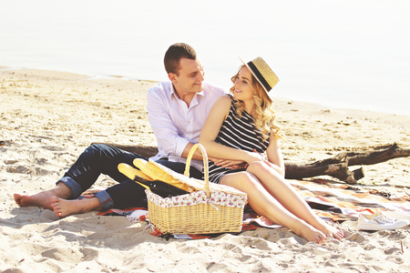 Totally in love with you. Horizontal shot of young man in casual wear and beautiful woman looking at each other and smiling while having picnic on beach. Zdjęcie Seryjne
