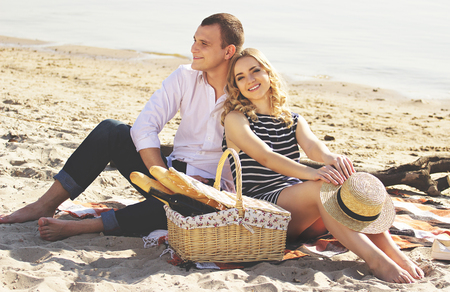 Loving couple. Horizontal shot of beautiful young woman looking to camera and smiling while sitting with boyfriend on beach and having picnic.
