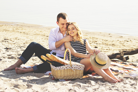 Love you so much. Horizontal shot of young man in casual wear hugging his smiling girlfriend and smiling while having picnic on the beach.