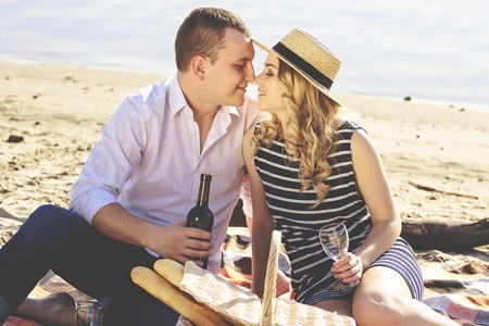 My honey girl. Portrait of handsome man in casual clothing keeping bottle with wine in his hand while sitting close face to face with his pretty girlfriend during romantic picnic on beach. Zdjęcie Seryjne