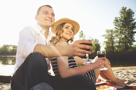 Happy together. Low-angle shot of beautiful and young couple in casual clothing looking away and smiling while keeping glasses with wine in their hands during romantic picnic.