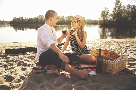 Love you so much. Horizontal shot of beautiful young couple keeping wineglasses with wine in hands and looking to each other while sitting on beach during romantic picnic.