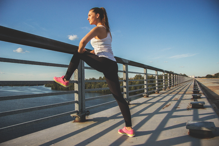 Stretching after workout. Horizontal shot of beautiful young woman in sports wear looking away while doing stretching on the bridge with blue sky on background.