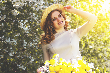 Charming beauty. Portrait of attractive young woman in dress adjusting hat on her head and smiling while keeping retro bike with flower basket. Zdjęcie Seryjne