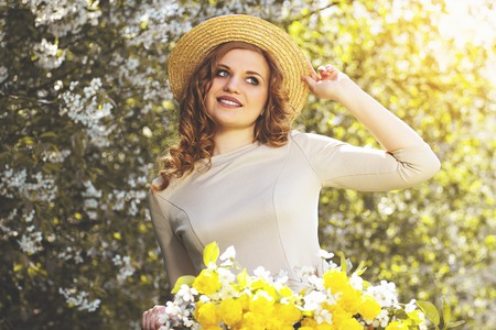 Pure beauty. Portrait of attractive young woman in dress adjusting hat on her head and smiling while keeping retro bike with flower basket.