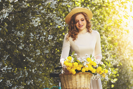 Beauty and nature. Portrait of young attractive woman in dress looking at retro bike and smiling while keeping flowers in basket on bike. Zdjęcie Seryjne