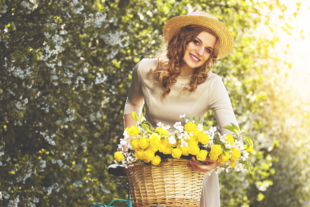 Riding on vintage bike. Portrait of gorgeous and young woman in dress looking to camera and smiling while riding on retro bike with flower basket. Zdjęcie Seryjne