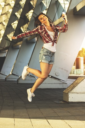 Beauty in motion. Full-length of attractive young woman in casual wear listening music and smiling while moving outdoors.