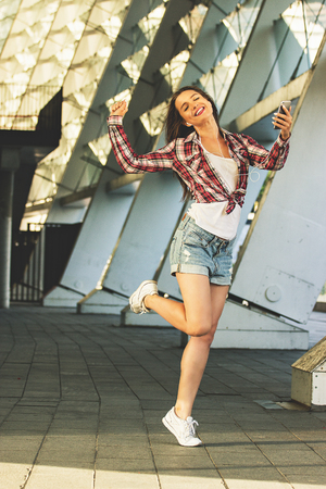 Young and carefree. Full-length of beautiful young woman in casual clothing listening music and smiling while moving outdoors.