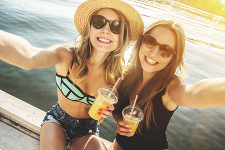 Capturing every summertime moment with friend. Two beautiful and young women taking selfie with lemonade on camera while sitting on the beach. Zdjęcie Seryjne