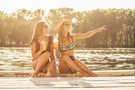 Hey, look over there! Two cheerful and young women drinking lemonade on wooden pier and looking away while one of them is pointing away.