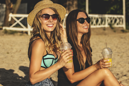 Happy summertime moments. Two young and beautiful women in swimsuits drinking lemonade and smiling while having fun on the beach. Zdjęcie Seryjne