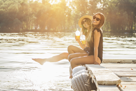 Young and carefree girls. Two young and attractive women in swimsuits drinking lemonade and smiling while having fun on wooden pier. Zdjęcie Seryjne