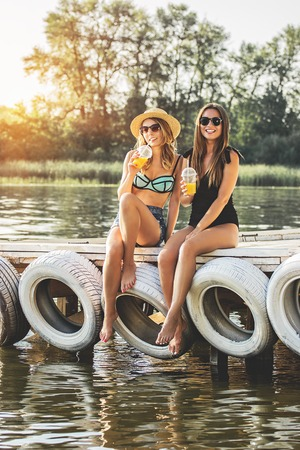 Happy summertime. Full-length of two beautiful young women in swimsuits drinking lemonade and smiling while having fun on wooden pier.